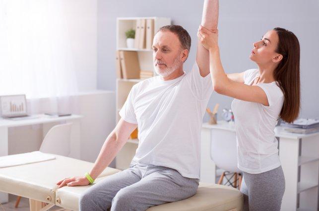 rehabilitantka prowadzi ćwiczenia z pacjentem