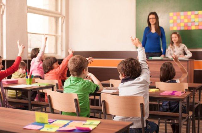 Klasa w szkole, dzieci odpowiadają nauczycielce.