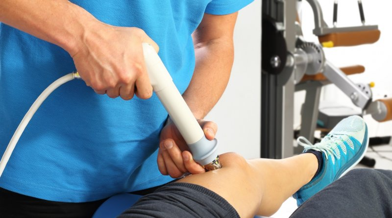 zdjęcie przedstawia pacjenta i rehabilitanta w czasie wykonywania zabiegu rehabilitacji