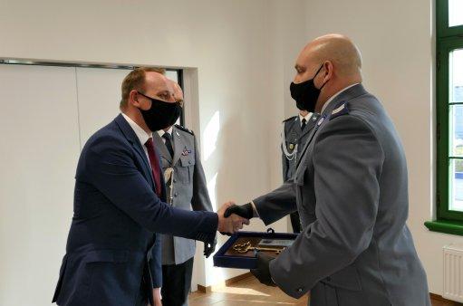 Na zdjęciu Burmistrz Łukasz Zbroszczyk przekazuje policji klucze do posterunkuu
