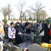 zdjęcie przedstawia grupę ludzi stojących na cmentarzu wśród pomników